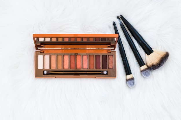 Colorful wooden eyeshadow palette with makeup brushes on white fur background