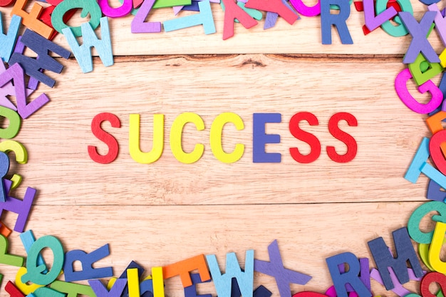 Colorful wooden letter of the alphabet and the word success isolated on wood background