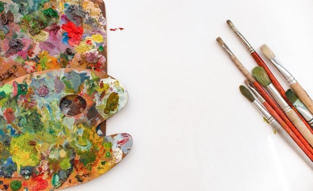 Красочная деревянная палитра, кисти и краски на белом фоне. место для текста