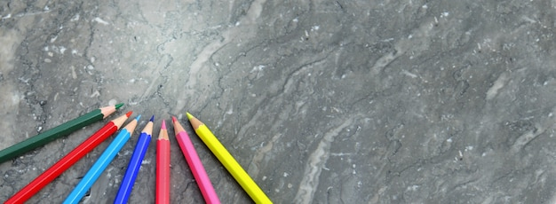 Colorful wooden pencils arranged on a grey  marble background in panoramic view  and copy space at the right