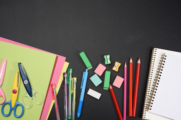 Colorful wooden pencils, notepads on a blank black chalk board, school stationery, copy space, back to school