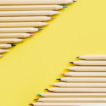 Colorful wooden pencils in a row on yellow backdrop