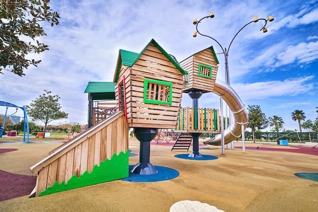 Красочная деревянная игровая площадка во дворе детского сада для игры на свежем воздухе