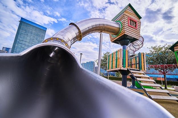 Красочная деревянная игровая площадка с горкой в детском парке для игр на свежем воздухе