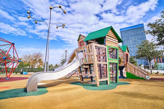 Красочная деревянная игровая площадка с горкой в детском парке для игр на открытом воздухе