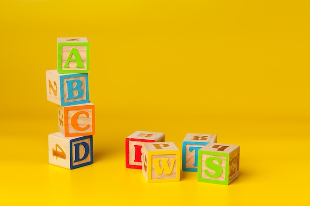 Colorful wooden surface blocks with letters on a yellow color