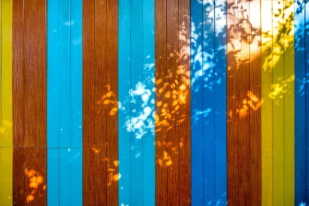 Colorful wooden texture wall background with sunlight