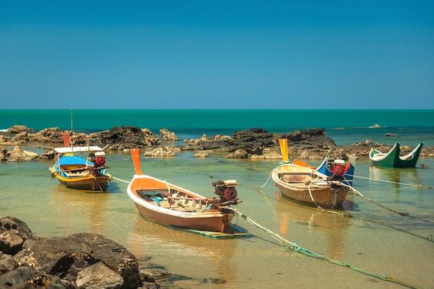 바다와 푸른 하늘을 배경으로 바위 사이에 다채로운 목조 태국 스타일 낚시 보트가 서 있습니다.