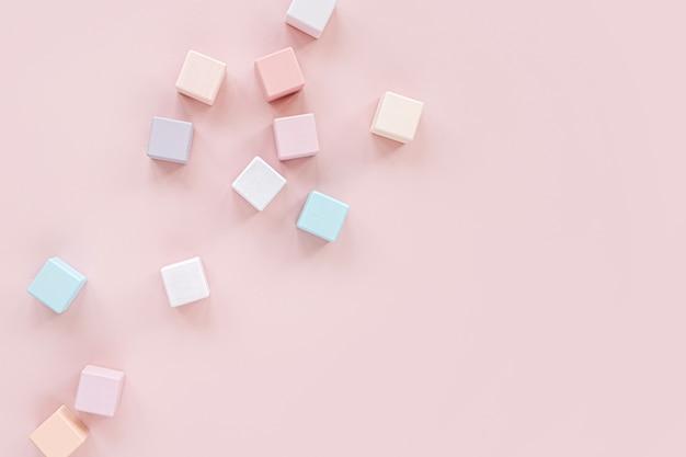 다채로운 나무 장난감 블록입니다. 파스텔 핑크 배경에 세련된 아기 장난감. 어린이를 위한 친환경 플라스틱 무료 장난감 액세서리. 평평한 평지, 평면도