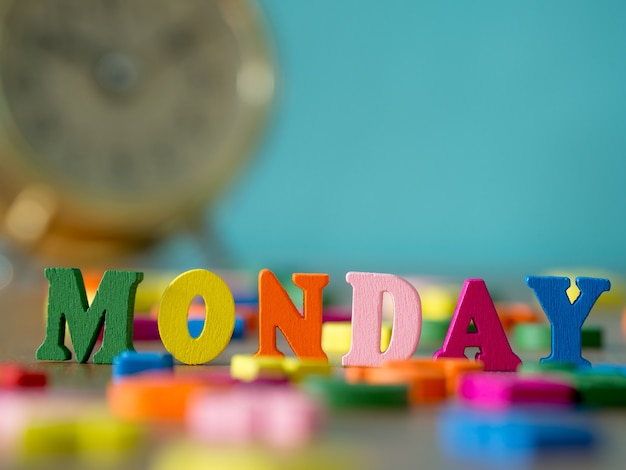 Colorful wooden word monday on wooden table and vintage alarm clock and background is powder blue.