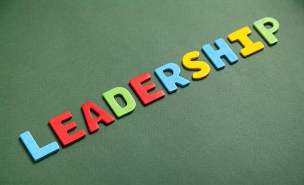Colorful word leadership on green background.