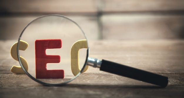 Colorful word seo with magnifying glass.