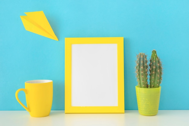 Colorful workplace with yellow paper plane and cactus
