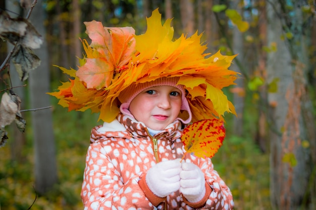 Colorful wreath from yellow leaves. smiling child in maple wreath outdoors. autumn walks