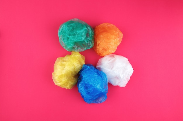Colorful wrinkled plastic bags on pink background