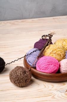 Красочные шарики пряжи и спицы на деревянном столе