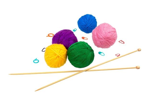 Красочные шарики пряжи с иглами и зажимом, изолированные на белом фоне.