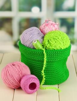 창 배경에 있는 나무 테이블에 녹색 바구니에 뜨개질을 위한 다채로운 원사
