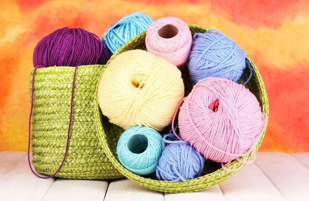 Colorful yarn for knitting in green basket on white wooden table on colorful background