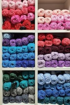 잡화 가게의 선반에 뜨개질을하기위한 다채로운 양모 원사. 니트 공예품 개념