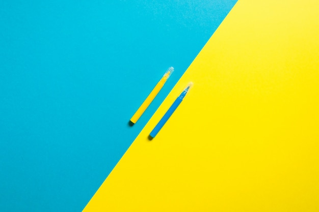 Colorful yellow and blue background with two pens