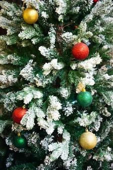 Шарики colorfull на елке, покрытой снегом. с новым годом и рождественским украшением фона.