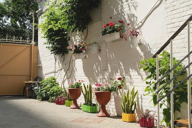 지중해 마을에 흰색 벽돌 벽이 있는 다채로운 꽃 거리