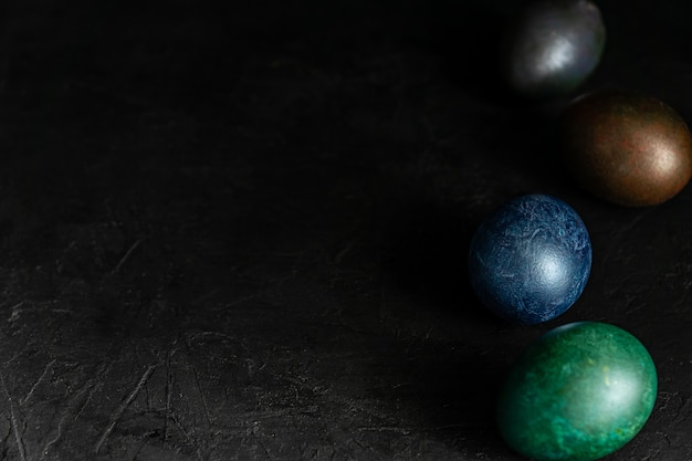 Colorfull marble painted easter eggs on black background. concept of minimal festive easter backdrop.