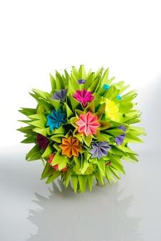白で隔離された虹の花からのカラフルな折り紙くす玉。いばらとバラ