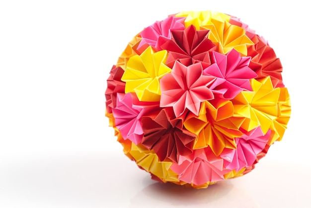 白で隔離された虹の花からのカラフルな折り紙くす玉