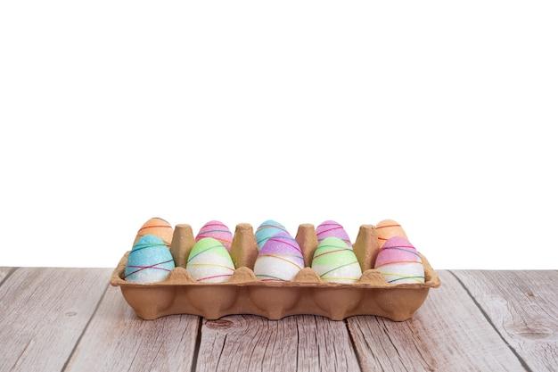 Красочно покрашенные пасхальные яйца на деревянном столе на белой предпосылке.