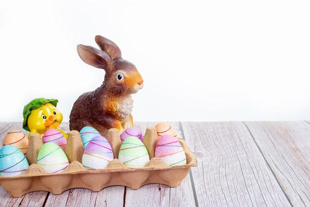 Красочно покрашенные пасхальные яйца с зайчиком на деревянном столе на белой предпосылке.