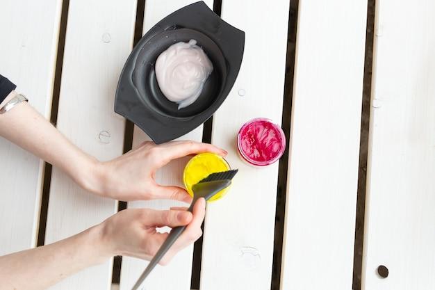 착색 및 헤어 스타일리스트 개념-미용사의 손은 머리카락, 상위 뷰에 대한 색상을 혼합합니다.