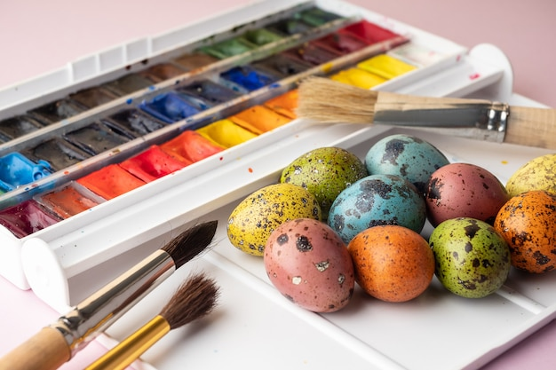 イースターエッグの着色。ピンクの背景にペイント、ブラシ、ウズラの卵。イースターのお祝いの準備、休日の装飾、背景。クリエイティブなコンセプト。