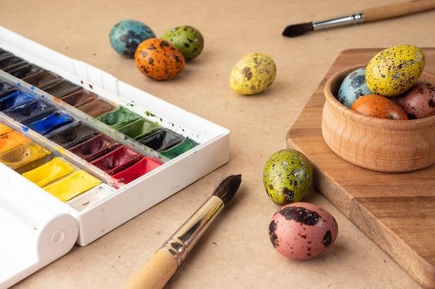 イースターエッグの着色。クラフトの背景に絵の具、ブラシ、ウズラの卵。イースターのお祝いの準備、休日の装飾、背景。クリエイティブなコンセプト。