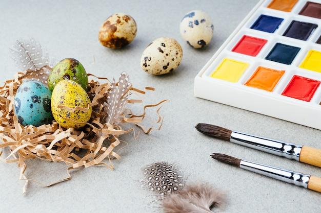イースターエッグの着色。灰色の背景に絵の具、ブラシ、ウズラの卵。イースターのお祝いの準備、伝統的な装飾、背景。クリエイティブなコンセプト。