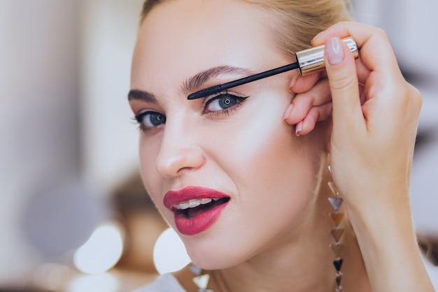 속눈썹 색칠. 그녀의 속눈썹을 채색하는 치과 괄호와 blonde-haired 매력적인 여자
