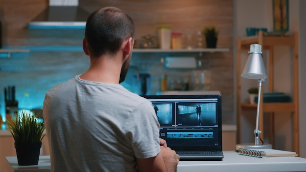 Colorist working remotely overtime from home using editing software sitting in front of laptop late at night. videographer processing audio film montage on professional in modern kitchen in midnight
