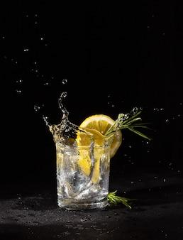 Бесцветный алкогольный напиток в стакане с долькой лимона и розмарина, всплеск