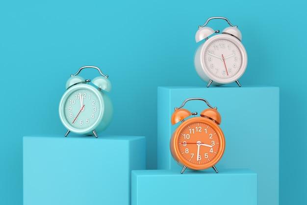 青い背景の青い台座、ステージ、表彰台、または柱の上に目覚まし時計を着色します。 3dレンダリング