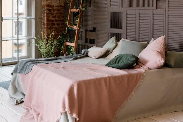 デザイナーインテリアと居心地の良い白とベージュの寝具を備えたスタイリッシュなベッドルームインテリアの小さなスペースの創造的な使用。最小限のロフトスタイル。インテリアのパステル調の柔らかいcolors.decorativeはしご