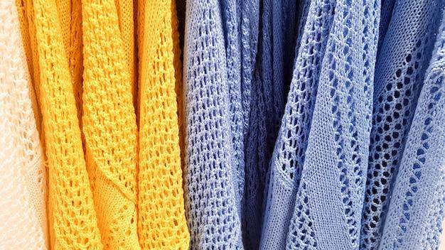 무지개의 색상입니다. 다양한 캐주얼 셔츠, 옷걸이에 있는 티셔츠. 다양한 밝은 색상의 천 면 클로즈업. 섬유 배경입니다.