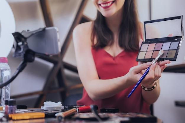 色合いの色。アイシェードの色についてのゴージャスな有名な美容ブロガーの撮影ビデオを笑顔