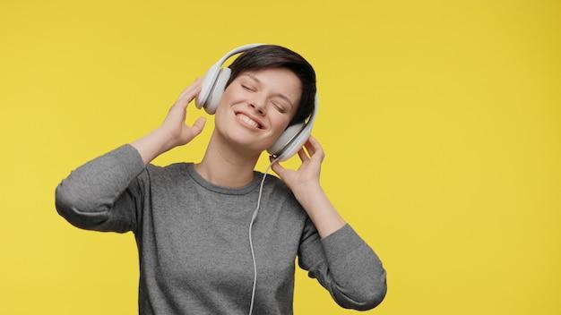 究極のグレーとヘッドフォンで若い女性を照らす2021年の色