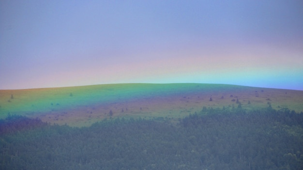 Colors of the rainbow covering the forest in the hills