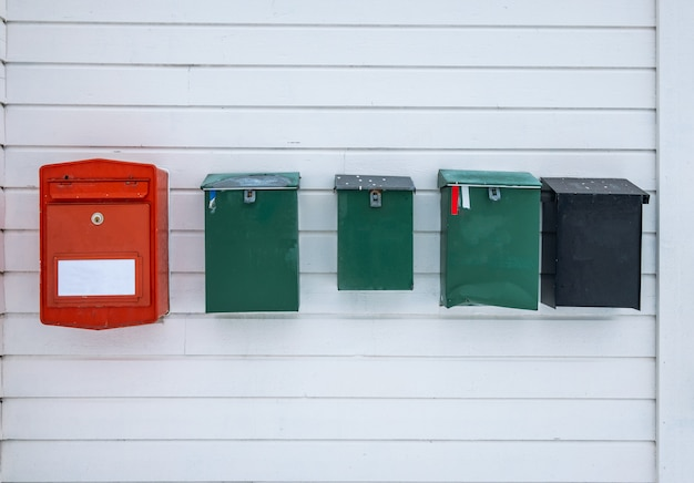 Colors vintage mailboxes along on wooden wall