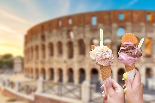 イタリアのアイスクリームジェラートを手にしたイタリア、ローマのコロッセオ