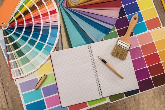 Colour palette with notepad on wooden table