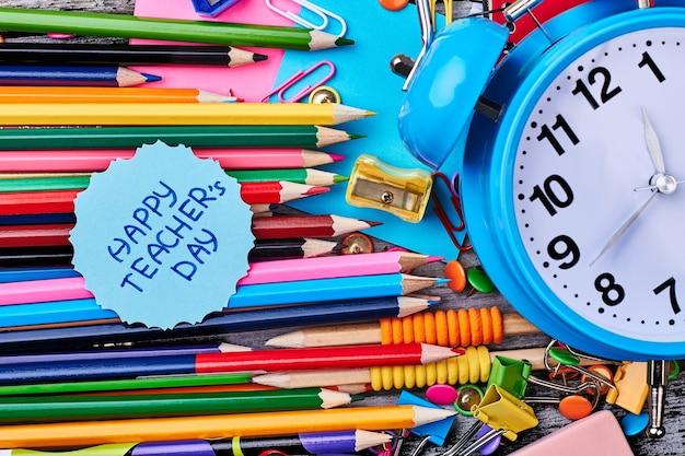 Цветные и графитовые карандаши. будильник и открытка. поздравьте всех ваших учителей.
