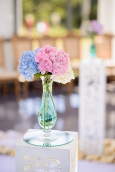 Coloured flowers in a glass vase on a white decorative wooden stand